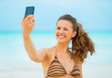 Smiling young woman taking self photo on beach Royalty Free Stock Images