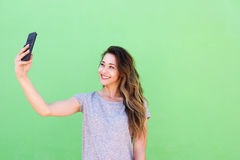 Smiling young woman taking selfie against green background Stock Photos