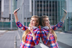 Smiling young woman taking selfie with mobile phone Stock Images