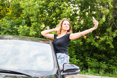 Smiling young woman taking selfie picture with smart phone camera outdoors in car Royalty Free Stock Photo