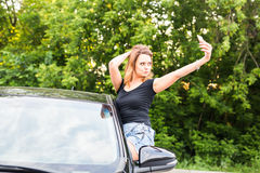 Smiling young woman taking selfie picture with smart phone camera outdoors in car Royalty Free Stock Photos