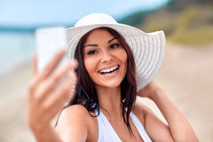 Smiling young woman taking selfie with smartphone Royalty Free Stock Photography