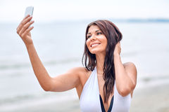 Smiling young woman taking selfie with smartphone Royalty Free Stock Image