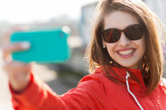 Smiling young woman taking selfie with smartphone Stock Photography