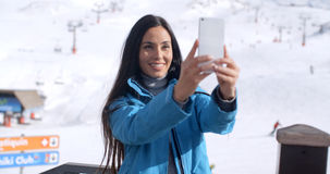 Smiling young woman taking a winter selfie Royalty Free Stock Image