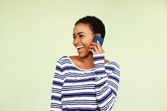 Smiling young woman talking with cell phone against green wall Stock Photos