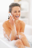 Smiling young woman talking cell phone in bathtub Royalty Free Stock Photography