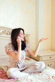 Smiling young woman talking mobile indoor Stock Photo