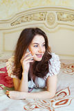 Smiling young woman talking mobile indoor Royalty Free Stock Image
