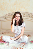 Smiling young woman talking mobile indoor Royalty Free Stock Photos