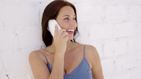 Smiling young woman talking on a mobile. Phone as she leans against a white brick wall in a trendy denim slack suit stock video footage