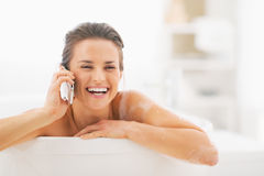 Smiling young woman talking mobile phone in bathtub Stock Photography