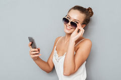 Smiling young woman talking on mobile phone and holding sunglasses. Smiling pretty young woman talking on mobile phone and holding sunglasses over gray Royalty Free Stock Photo