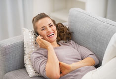 Smiling young woman talking mobile phone while laying on couch Stock Photo