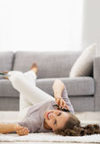 Smiling young woman talking mobile phone while laying on floor Stock Image