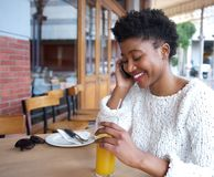 Smiling young woman talking on mobile phone at restaurant Royalty Free Stock Image