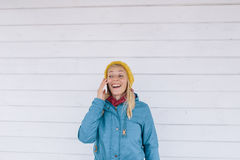 Smiling young woman talking on the phone. woman in yellow knitted hat and a blue jacket using cell phone Royalty Free Stock Image