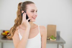 Smiling young woman talking on smartphone. In the kitchen at home Stock Image