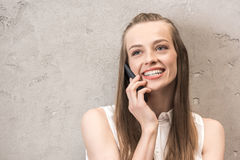Smiling young woman talking on smartphone and looking away Stock Photos
