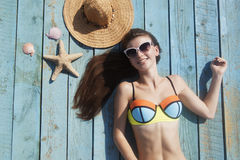 Smiling young woman tans on the beach. On the bright blue wood background Royalty Free Stock Photos