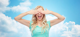 Smiling young woman or teen girl covering her eyes Stock Photography