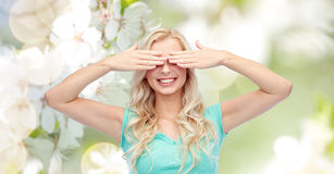 Smiling young woman or teen girl covering her eyes Royalty Free Stock Image