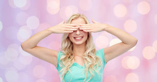 Smiling young woman or teen girl covering her eyes Royalty Free Stock Images