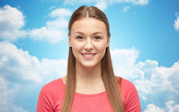 Smiling young woman or teenage girl over blue sky Royalty Free Stock Image