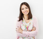 Smiling Young woman teenager arms crossed, in pink royalty free stock photo
