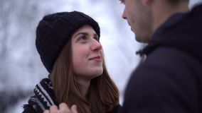 Smiling young woman with teeth braces and tall man looking into each other`s eyes in winter clothing. Man caress hair of. His girlfriend. Happy couple in love stock video