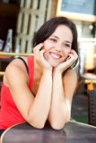Smiling young woman on terrace. Beauty sit on a terrace in Paris smiling to someone coming Royalty Free Stock Images