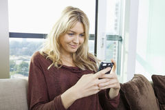 Smiling young woman text messaging at home Stock Photos