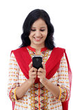 Smiling young woman texting  against white Royalty Free Stock Image