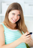 Smiling young woman texting on her cellphone Stock Photo