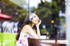 Smiling young woman thinking in cafe shop Royalty Free Stock Image