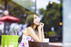 Smiling young woman thinking in cafe shop Royalty Free Stock Images