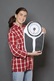 Smiling young woman thrilled by her weight loss Stock Photos