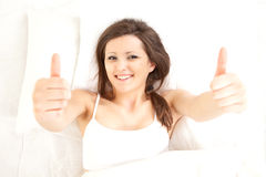 Smiling young woman with thumbs up in bedding Royalty Free Stock Photography