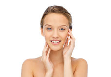 Smiling young woman touching her face Stock Photo