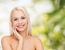 Smiling young woman touching her face skin Royalty Free Stock Images