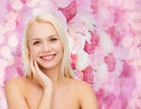 Smiling young woman touching her face skin Stock Image