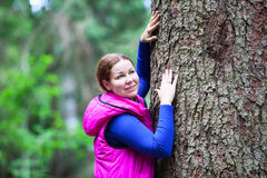 Smiling young woman touching stem of big pine Royalty Free Stock Image
