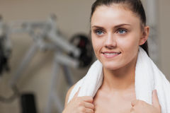 Smiling young woman with towel around neck in gym Royalty Free Stock Image