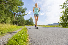 Smiling young woman trains on a road in the forest Stock Image