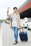 Smiling young woman with travel bag over taxi Royalty Free Stock Photo