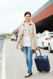 Smiling young woman with travel bag over taxi Stock Photo