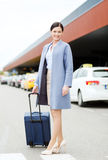 Smiling young woman with travel bag over taxi Royalty Free Stock Photos