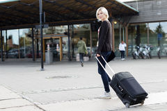 Smiling young woman traveling with a wheeled suitcase Stock Photos