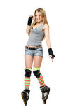 Smiling young woman tries to keep his balance. On roller skates Royalty Free Stock Photography