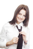 Smiling young woman tying a tie Royalty Free Stock Image
